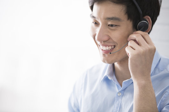 Cheerful young Chinese businessman with headset in office