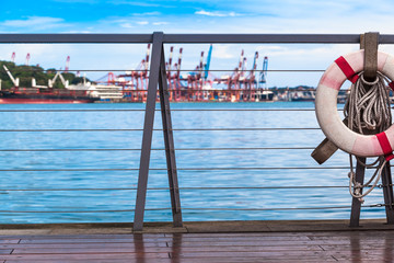 Sea Travel Scene / View from wooden pier with safety railing and life buoy to harbor wharf of Keelung, Taiwan