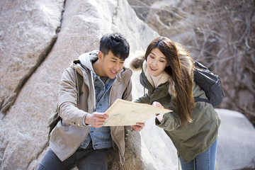 Happy young Chinese couple looking at a map outdoors