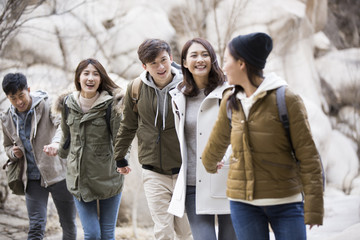 Happy young Chinese friends holding hands on winter outing