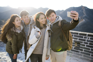 Happy young Chinese friends taking selfies on the Great Wall