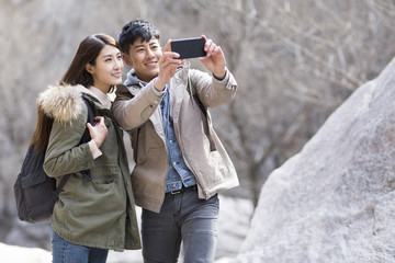 Happy young Chinese couple taking selfies outdoors in winter
