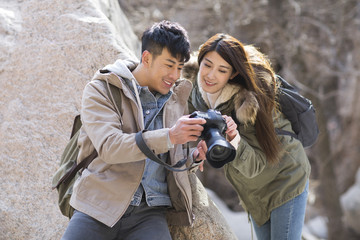 Happy young Chinese couple photographing outdoors in winter