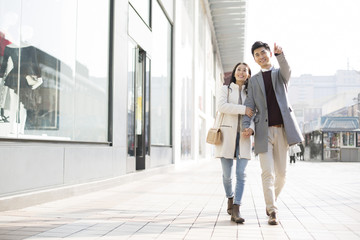 Cheerful young Chinese couple holding hands walking