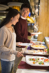 Cheerful young Chinese couple taking food from buffet table