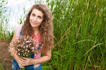 Happy beautiful woman with bouquet of pink flowers as gift in summer