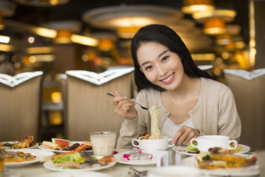 Cheerful young Chinese woman having buffet dinner