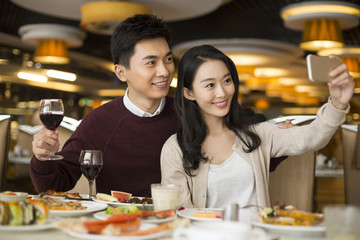 Cheerful young Chinese couple having buffet dinner
