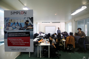 Students work in their web development class as part of professional training at the Simplon.co school specialized in digital sector in Montreuil, near Paris