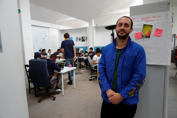Raphael Roig, territorial development officer at Simplon.co, poses in front of a web development class during an interview with Reuters at the Simplon school specialized in digital sector in Montreuil