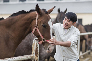 Cheerful young Chinese man and horse