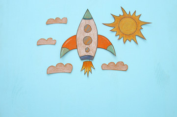 Rocket cut from paper and painted over wooden blue background.