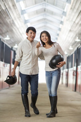 Cheerful young Chinese couple in horse stable