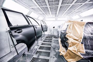 Painting the car in black color in the paint chamber on the service..
