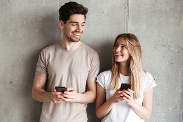 Modern sociable people man and woman smiling while both using mobile phones, isolated over concrete gray wall indoor