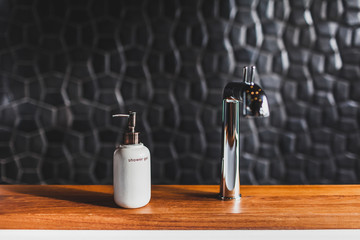 White metal bottle of shower gel on wooden edge of bath in modern hotel room with textured black wall