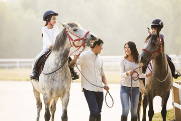 Cheerful young Chinese family riding horses