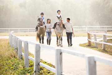 Cheerful young Chinese family riding horse