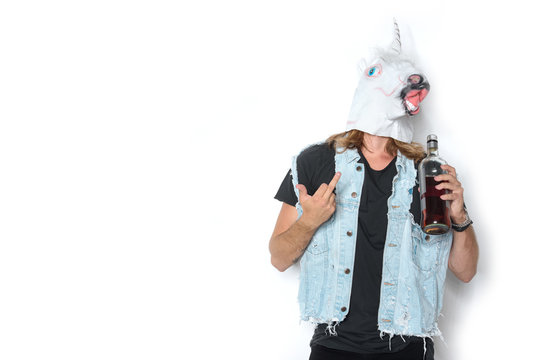 man in unicorn mask and denim vest with bottle of rum showing middle finger on white