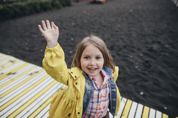 Portrait of smiling little girl on boardwalk on black lava beach