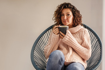 Attractive curly hair female sitting on chair and drinks coffee.
