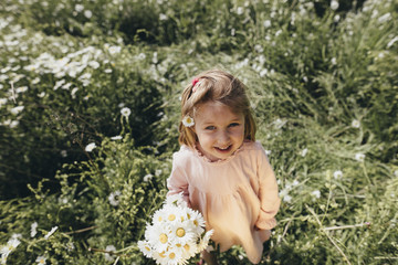 Portrait of little girl with bunch of picked flowers on a meadow