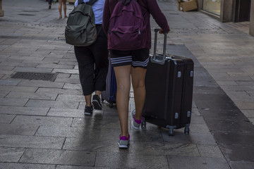 dos turistas con sus maletas por la ciudad