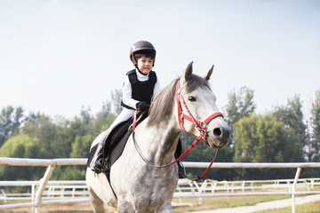 Cheerful little Chinese boy riding horse