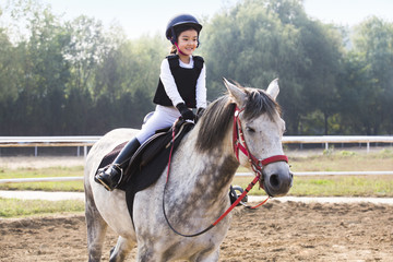 Cheerful little Chinese girl riding horse