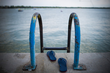 Pool ladder with selective focus in the lake with slippers without people.