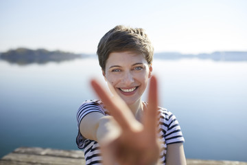 Portrait of smiling woman in front of lake showing victory sign