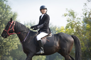 Young Chinese man riding horse