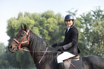 Cheerful young Chinese man riding horse