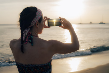 Thailand, Koh Lanta, woman on the beach taking photo with cell phone at sunset