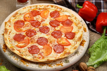 Pizza thin with smoked sausage, cheese, spices and tomatoes on a wooden stand. Cherry tomatoes and sweet peppers, lettuce leaves. Close-up