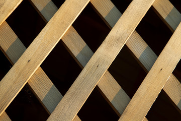 Lattice made of wooden slats against a dark background. Background for the designer.