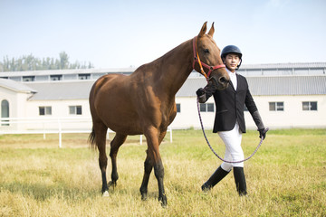 Chinese male rider walking on grassy field with horse