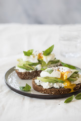 Toast with ricotta, avocado and a poached egg on top