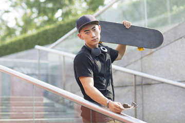 Young Chinese man with headphones carrying a skateboard on his shoulder