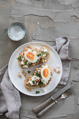 Plate with toast, white beans and a boiled egg