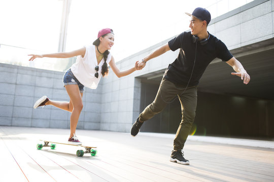 Cheerful young Chinese couple skateboarding