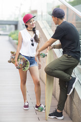 Cheerful young Chinese couple with skateboard talking