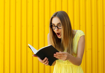 Pretty smiley surprised girl student with book wearing funny toy glasses over yellow background