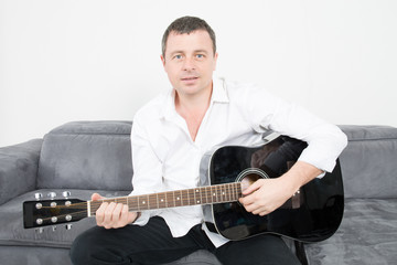 handsome man play guitar in home sofa in house