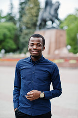 African  man posed at street of city wear on blue shirt and black pants.
