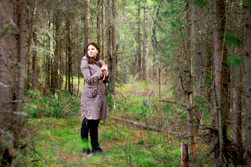 A woman in a brown cloak in the deep forest.