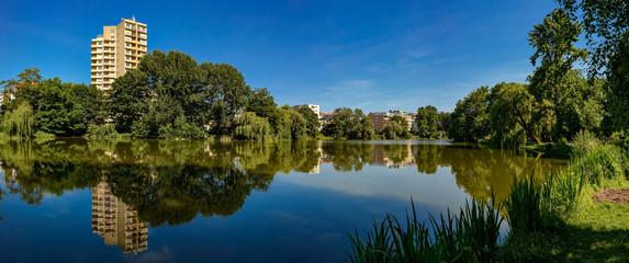 Ein Hochhaus spiegelt sich im sommerlichen Lietzensee (südlicher Teil) in Berlin-Charlottenburg - Panorama aus 8 Einzelbildern Fototapete