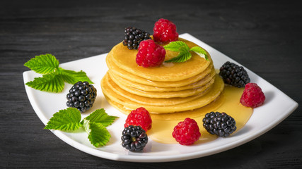 pancakes with honey raspberries and blackberries on a black wooden background