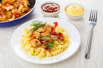 Fried meat, sweet pepper, fusilli in plate, mayonnaise, ketchup, fork