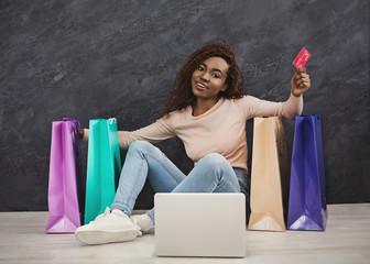 Young african woman shopping online at home